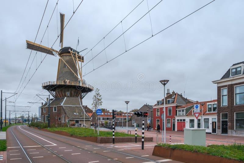 Uma estrada nova e um bonde ao longo do moinho de vento velho de Roos da cidade na lou?a de Delft, os Pa?ses Baixos imagens de stock