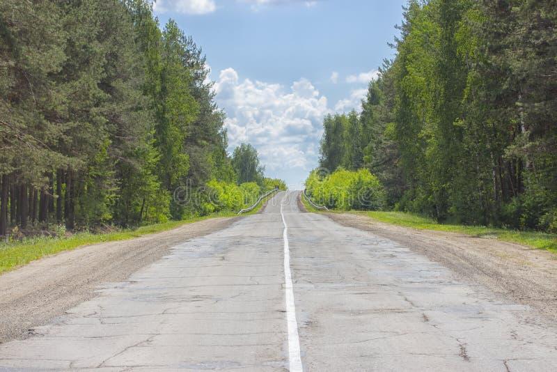 Uma estrada rural pobre-pavimentada da dois-pista, floresta decíduo, céu nebuloso, estrada ao horizonte imagens de stock