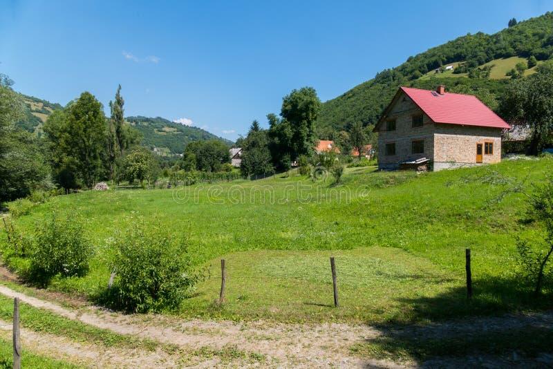 Uma estrada rural que corre ao lado da jarda com um gramado verde e uma casa que estão nas profundidades no monte imagens de stock royalty free