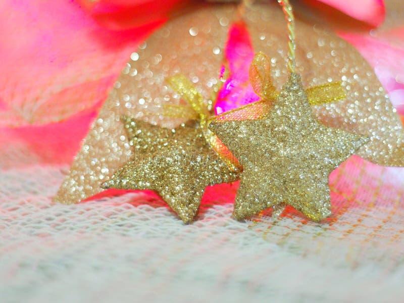 Uma estrela do ouro para decorações do Natal na tela da malha e em um fundo colorido com o conceito da celebração, Natal, ano nov fotografia de stock