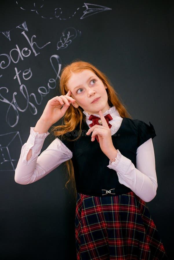 Uma estudante com cabelo longo vermelho em uma farda da escola está a administração da escola próxima imagens de stock