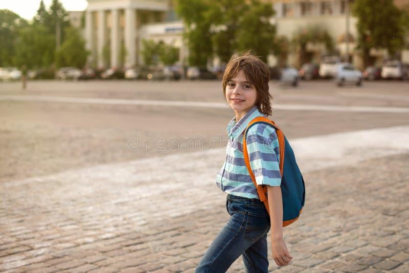 Uma estudante loura, vestindo em uma camisa e em calças de brim, caminhadas com um kn imagens de stock