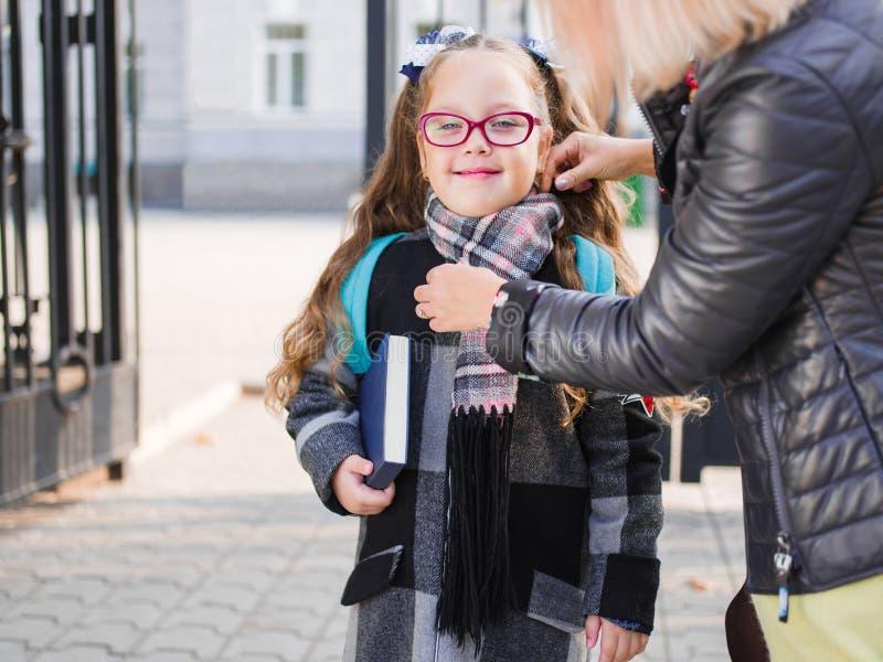 Uma estudante pequena no uniforme com uma pasta vai à escola foto de stock royalty free