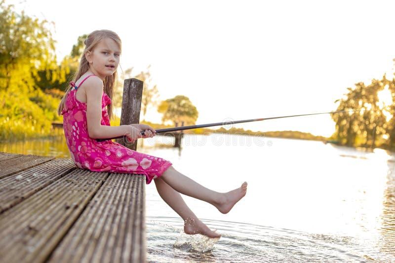Uma estudante senta-se em um molhe por um lago e por peixes fotos de stock