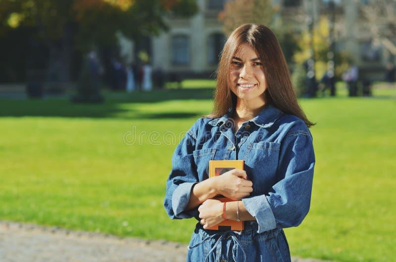 Uma estudante universitário fêmea que lê um livro ao encontrar-se imagem de stock