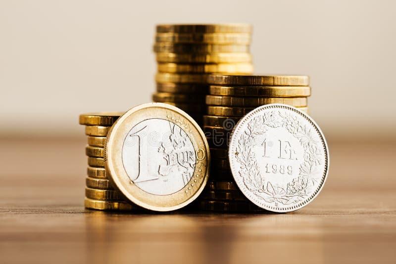 Uma euro- moeda e uma franquia suíça fotos de stock
