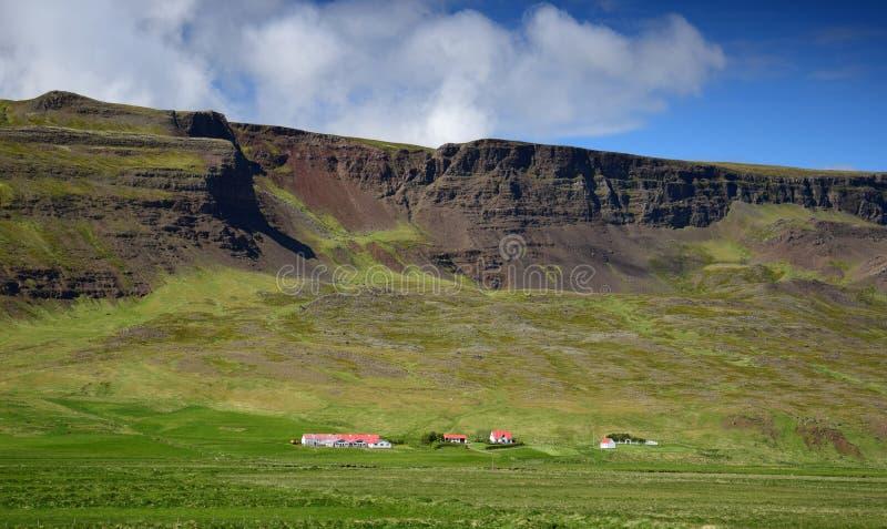 Uma exploração agrícola em Islândia no pé de uma cordilheira imagens de stock