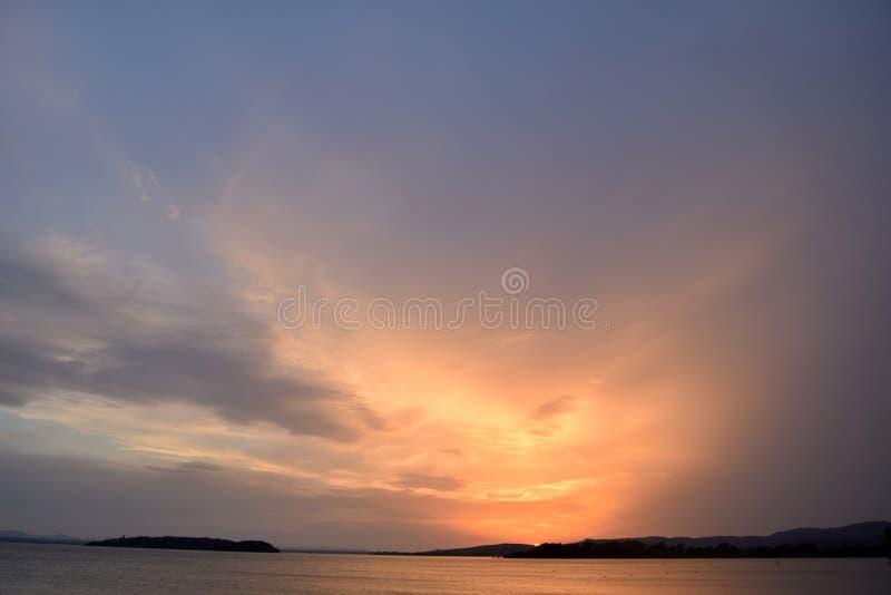 Uma explosão das cores no por do sol no lago Trasimeno em Úmbria - I imagem de stock