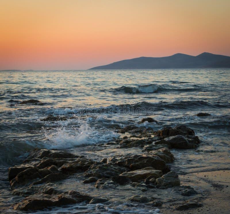 Uma exposição longa do mar como quebra sobre as rochas e a praia no por do sol imagens de stock
