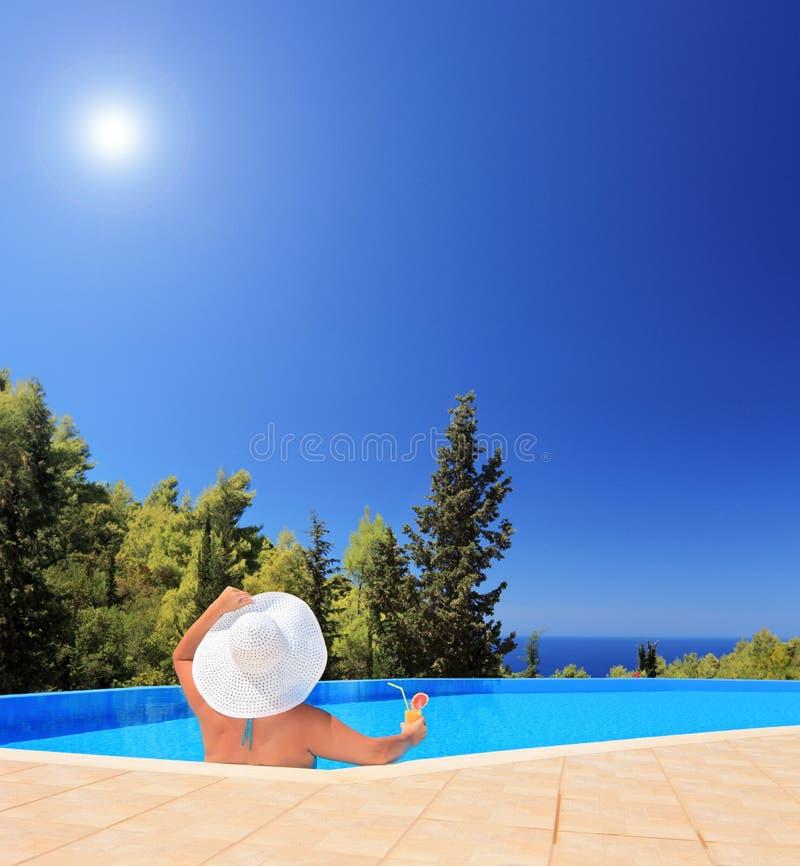 Uma fêmea nova que relaxa em uma piscina e que guardara um cocktail fotografia de stock royalty free