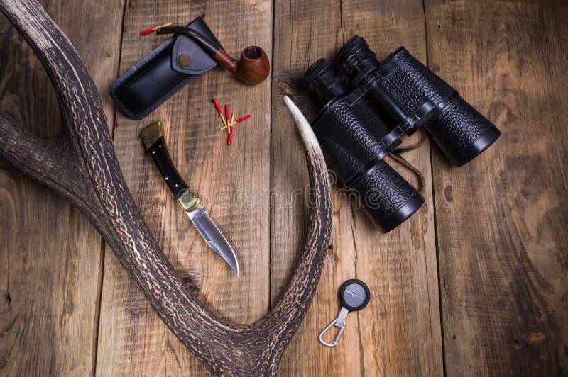 Uma faca de caça, binóculos e um berço para o cigarro Chifre e árvore dos cervos no fundo foto de stock royalty free