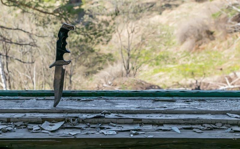 Uma faca velha terrível do combate colada no peitoril arruinado da janela fotografia de stock