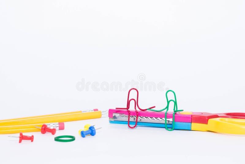 Uma fala de dois clipes de papel, sentando-se em um ziguezague scissors com os lápis no fundo Vida diminuta da escola e de volta  foto de stock