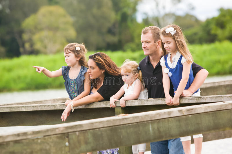 Uma família com crianças novas junto pelo lago fotos de stock royalty free