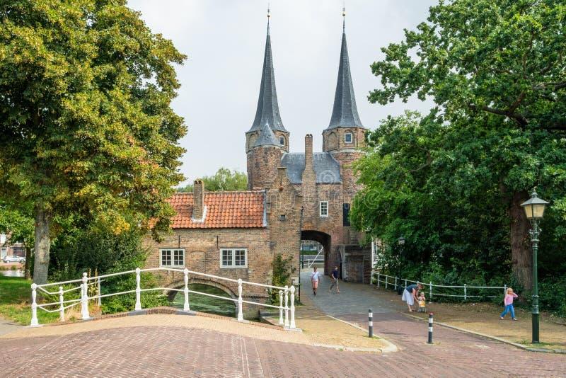 Uma família com jovens crianças visita a porta oriental uma porta velha da louça de Delft, os Países Baixos da cidade imagem de stock