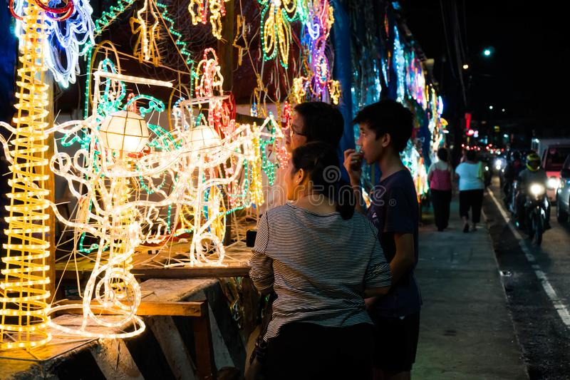 Uma família está tentando escolher um projeto para a decoração do Natal para sua casa imagem de stock