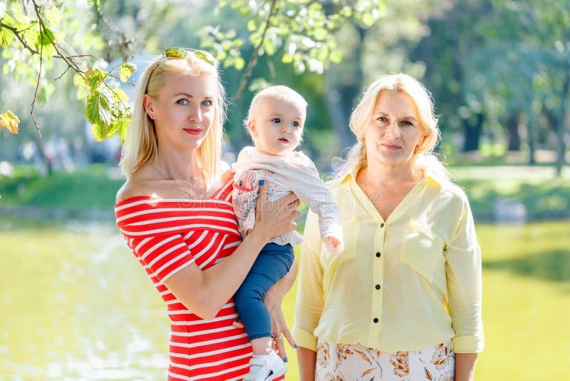 Uma família feliz de três gerações, mãe, filha, avó e neta pequena do bebê, está estando junto no bri fotografia de stock