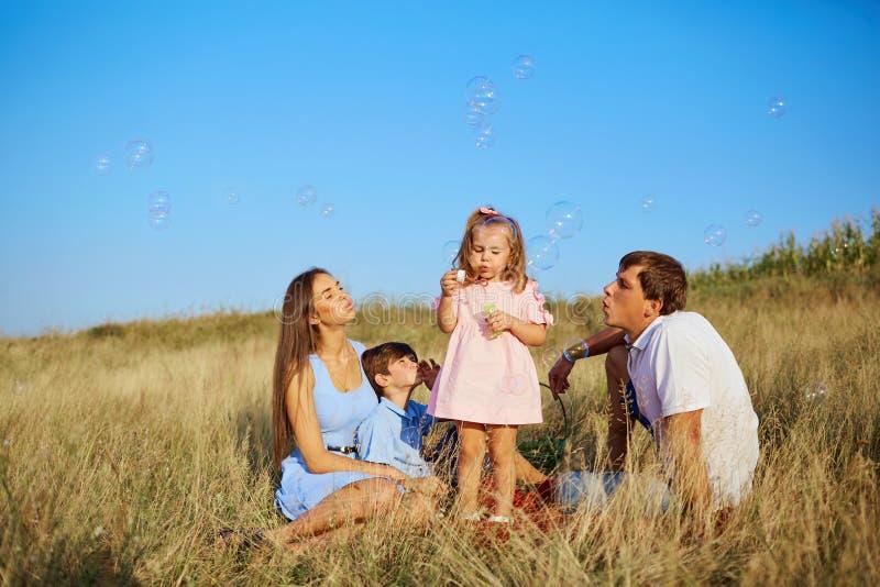 Uma família feliz nas bolhas de sabão de sopro da natureza fotografia de stock royalty free