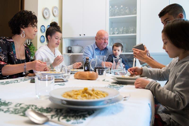 Uma família italiana tem o almoço com massa foto de stock