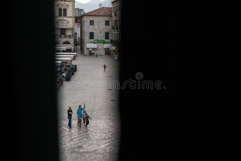 Uma fam?lia na cidade velha de Kotor, Montenegro, tiro atrav?s dos obturadores entreabertos da janela fotos de stock