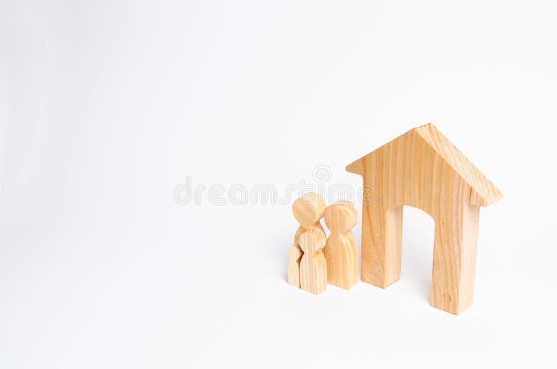 Uma família nova com crianças está estando perto de uma casa de madeira O conceito de uma família forte, a continuação da família fotografia de stock