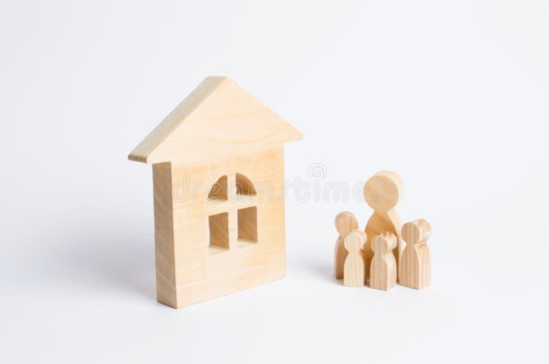 Uma família nova com crianças está estando perto de uma casa de madeira O conceito de uma família forte, a continuação da família imagem de stock