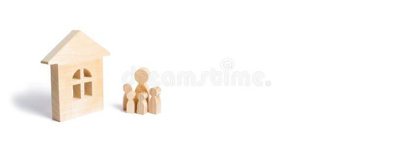 Uma família nova com crianças está estando perto de uma casa de madeira O conceito de uma família forte, a continuação da família fotografia de stock royalty free