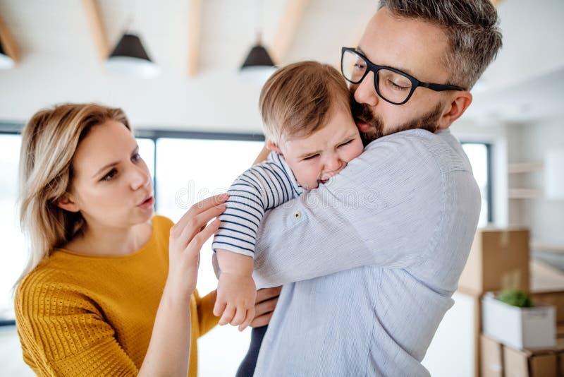 Uma família nova com uma menina de grito da criança que está dentro em casa fotos de stock