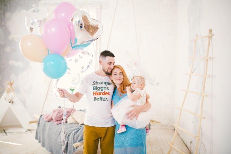 Uma família nova de três povos, de paizinho do ` s da mamã e de bebê de um ano do ` s da filha está dentro da sala Guardando um b fotos de stock royalty free