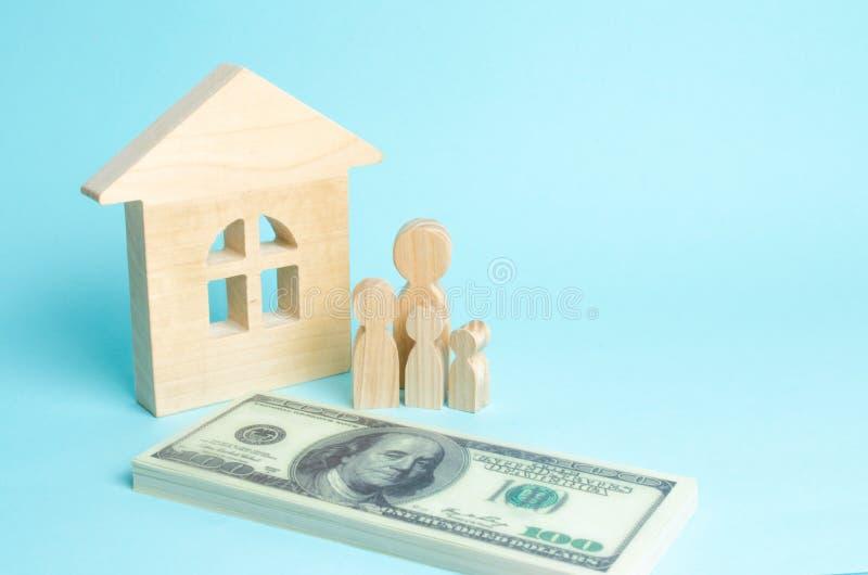 Uma família nova está perto de uma casa de madeira e com um pacote de dinheiro O conceito de uma família forte, a continuação do  foto de stock royalty free