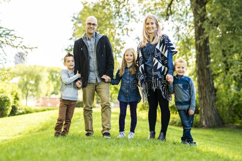Uma família nova feliz fora na natureza verde imagem de stock
