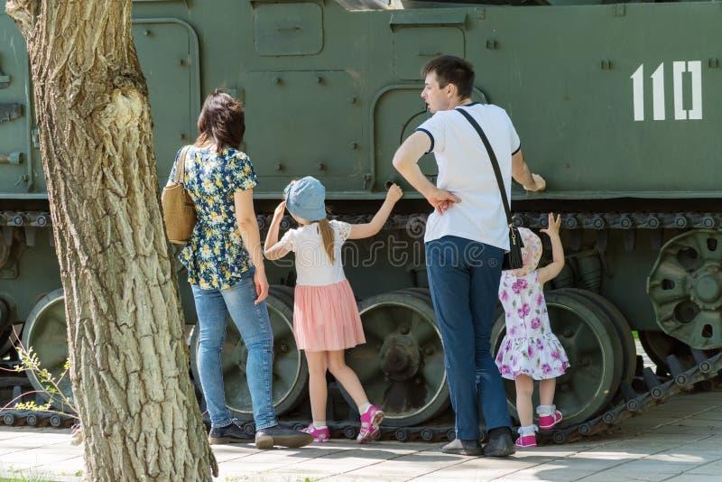Uma família nova na exposição do equipamento militar imagem de stock royalty free