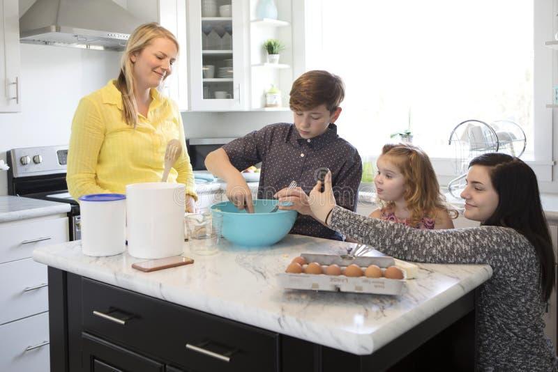 Uma família que coze junto em sua cozinha moderna foto de stock
