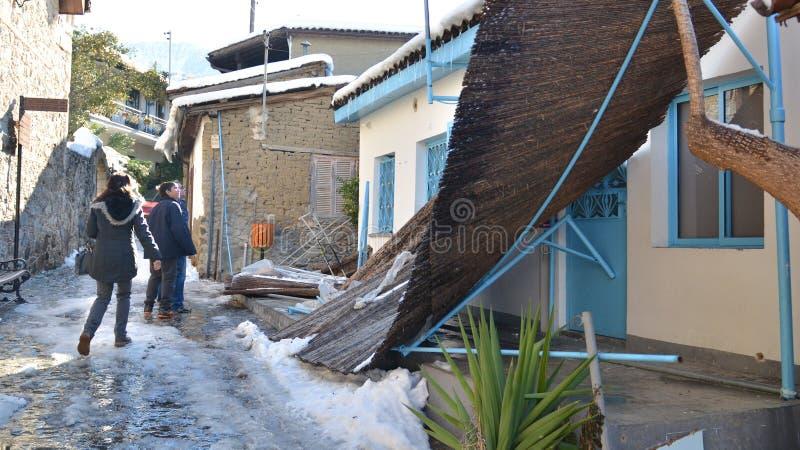 Uma família que olha uma casa destruída da queda de neve imagens de stock royalty free