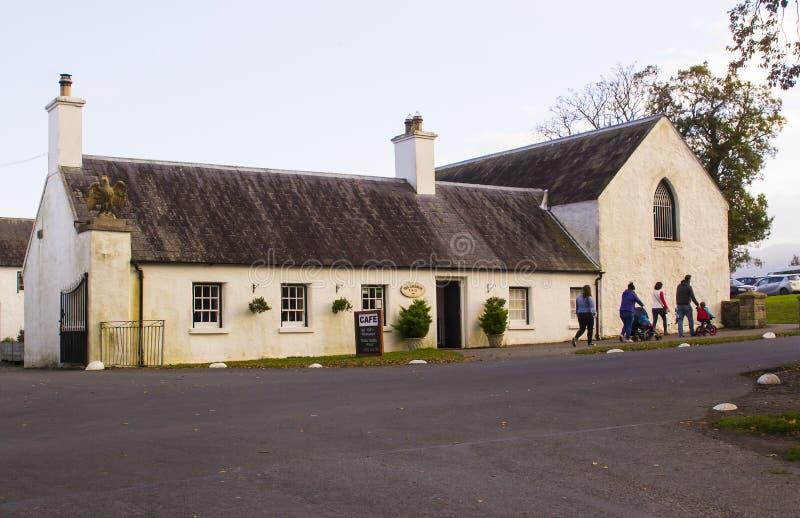 Uma família que sae da loja pequena do chá no parque do país de Castlewellan durante uma ruptura meados de da escola do termo imagem de stock
