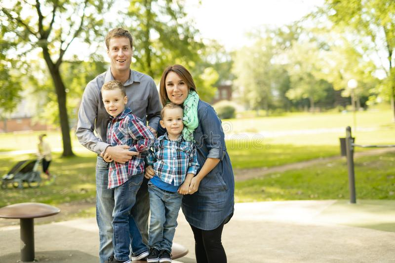 Uma família que tem o divertimento com childs no campo de jogos foto de stock