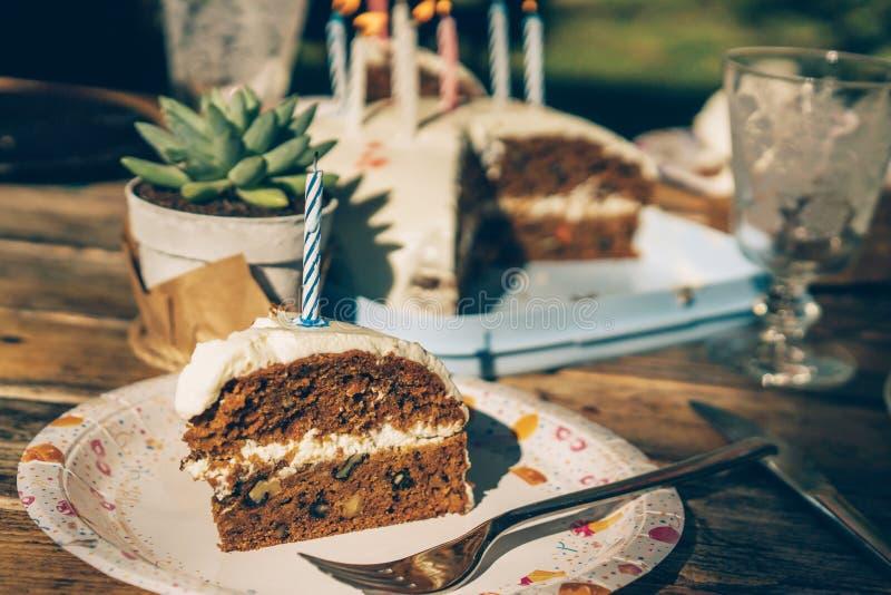 Uma fatia de bolo de cenoura caseiro com uma vela imagens de stock