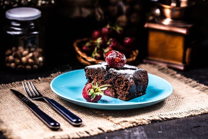 Uma fatia de brownie com morangos em uma placa azul fotografia de stock