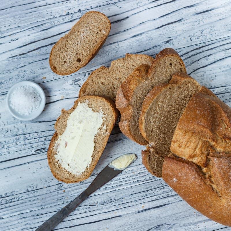 Uma fatia de p?o de centeio com manteiga em um fundo de madeira ? um close-up imagem de stock royalty free