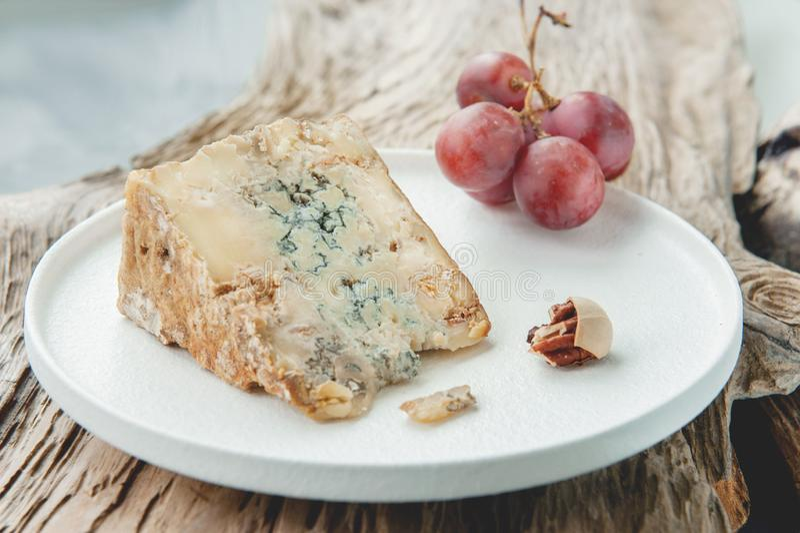 Uma fatia de queijo envelhecido azul do queijo Stilton em uma tabela de madeira O queijo é servido com grandes uvas Qualidade dos fotografia de stock