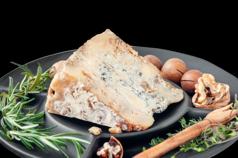 Uma fatia de queijo envelhecido azul do queijo Stilton em uma tabela de madeira O queijo é servido com nozes-pecã Qualidade dos p imagens de stock royalty free