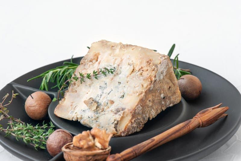 Uma fatia de queijo envelhecido azul do queijo Stilton em uma tabela de madeira O queijo é servido com nozes-pecã Qualidade dos p fotografia de stock