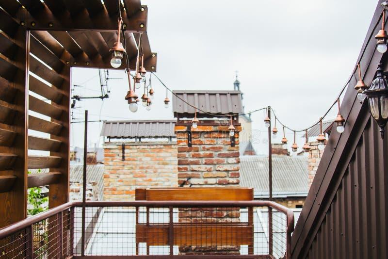 Uma festão das ampolas brancas pendura no telhado ennobled da casa miradouro de madeira no housetop que negligencia o vizinho foto de stock royalty free