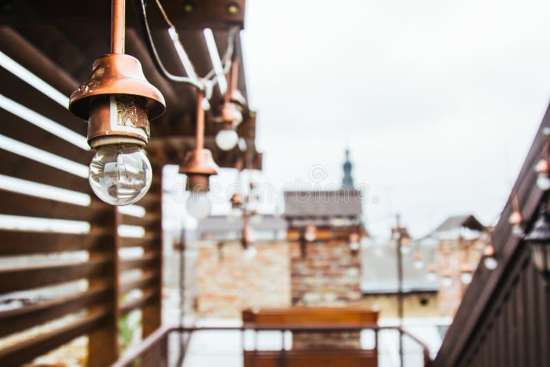 Uma festão das ampolas brancas pendura no telhado ennobled da casa miradouro de madeira no housetop que negligencia o vizinho fotografia de stock
