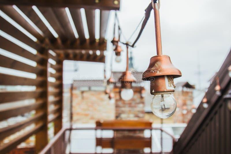 Uma festão das ampolas brancas pendura no telhado ennobled da casa miradouro de madeira no housetop que negligencia o vizinho imagem de stock