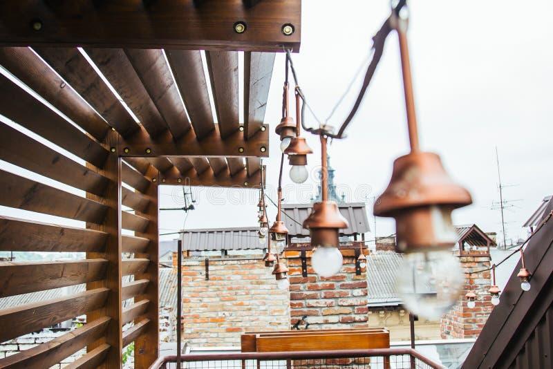 Uma festão das ampolas brancas pendura no telhado ennobled da casa miradouro de madeira no housetop que negligencia o vizinho imagem de stock royalty free