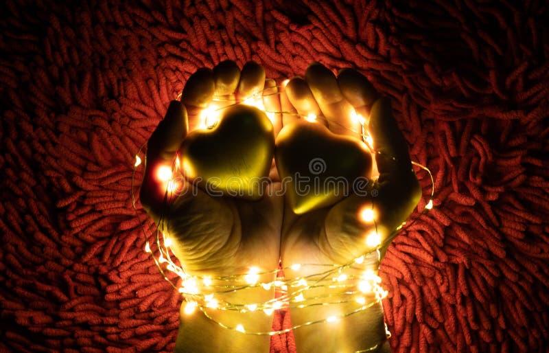 Uma festão morna da luz da cor que cerca duas mãos que guardam corações Dia do `s do Valentim imagem de stock royalty free