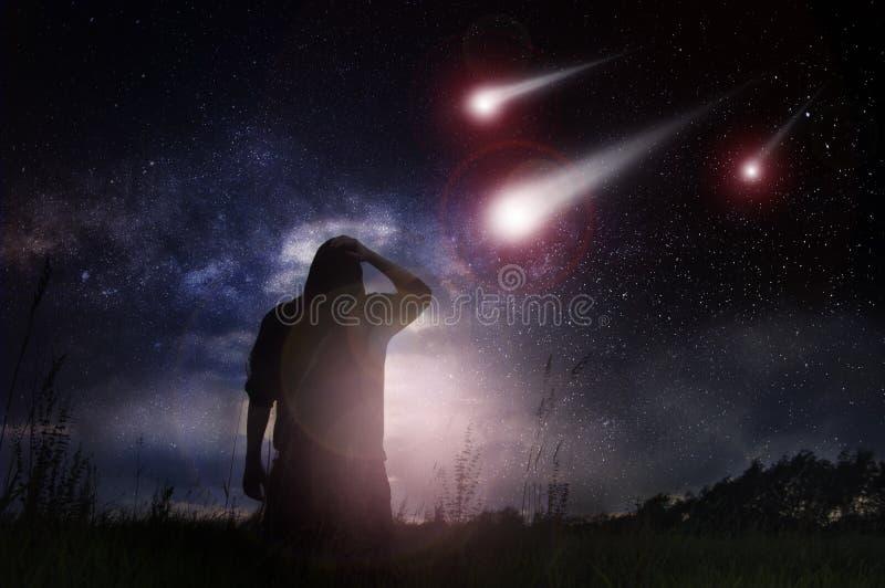 Uma ficção científica edita de uma posição do homem em um campo enquanto os meteorito se apressam para a terra na noite com prota imagens de stock