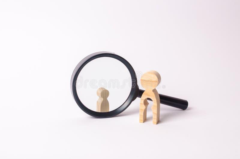 Uma figura de madeira de uma mulher está perto da lupa, atrás de que está uma criança O conceito de encontrar uma criança fotografia de stock royalty free