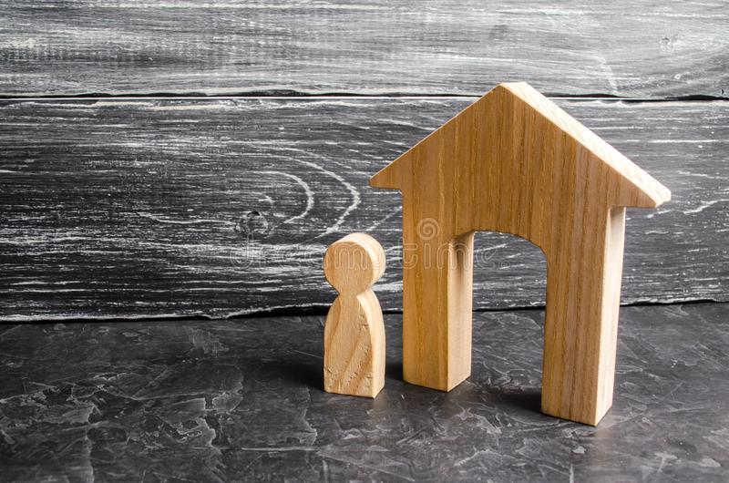 Uma figura de madeira de um homem está perto de uma casa de madeira em um fundo concreto cinzento Conceito de bens imobiliários,  fotos de stock royalty free